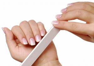 Body-care of hands. Woman polishing nails with thó nail file.
